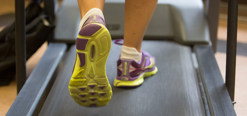Woman walking on treadmill in athletic shoes