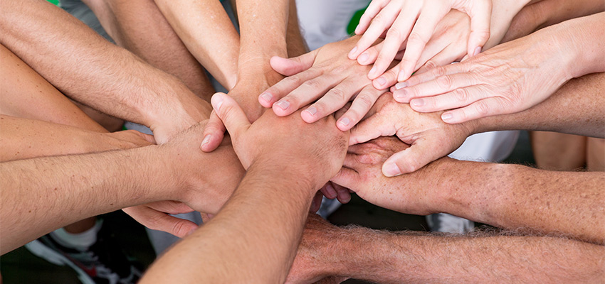 Hands all in together in a team huddle