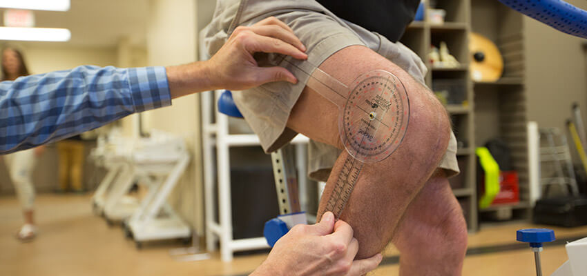 Staff member measuring angle of post-surgery knee